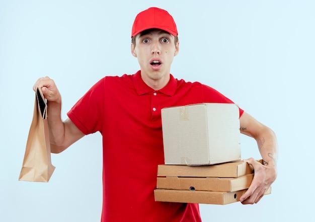 Giovane fattorino in uniforme rossa e pacchetti di scatola del cappuccio che guardano in avanti confuso in piedi sul muro bianco
