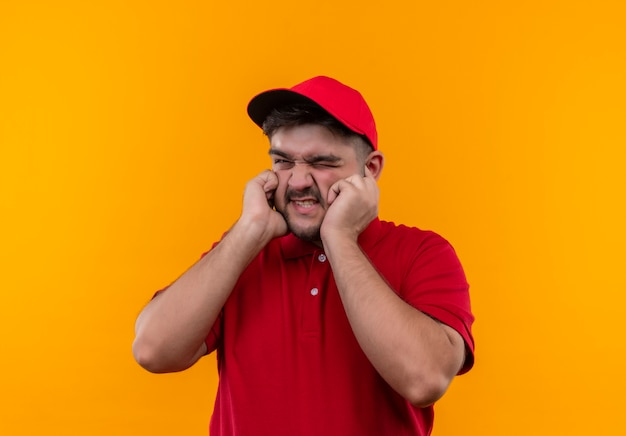 Young delivery man in red uniform and cap closing eras with fingers with annoyed expression for the noise