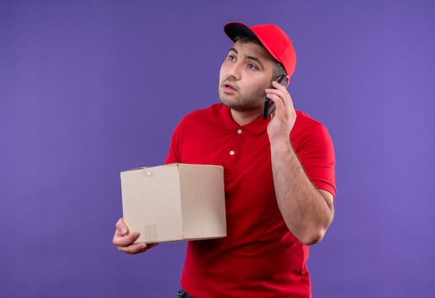 Giovane fattorino in uniforme rossa e cappuccio che tiene il pacchetto della scatola che osserva da parte con la faccia seria mentre parla al telefono cellulare in piedi sopra la parete viola