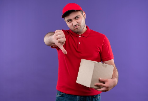 Giovane fattorino in uniforme rossa e berretto che tiene il pacchetto della scatola, mostrando i pollici verso il basso con la faccia accigliata in piedi sul muro viola