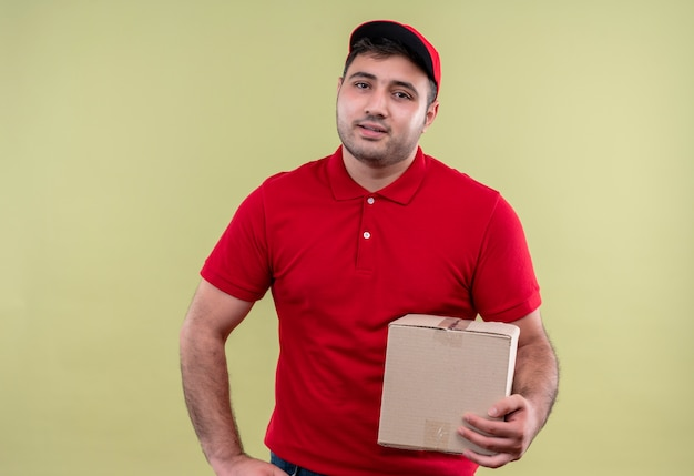 Young delivery man in red uniform and cap holding box package smiling friendly standing over green wall