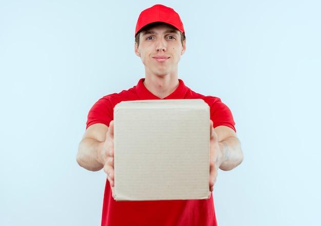 Giovane fattorino in uniforme rossa e cappuccio che tiene la scatola di cartone guardando in avanti con espressione fiduciosa in piedi sopra il muro bianco