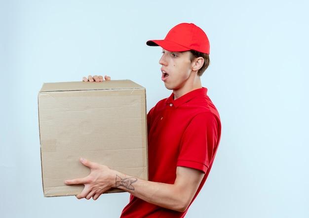Giovane fattorino in uniforme rossa e cappuccio che tiene la scatola di cartone guardandolo sorpreso in piedi sopra il muro bianco