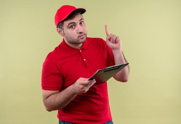 Giovane fattorino in uniforme rossa e cappuccio che tiene appunti rivolto verso l'alto con il dito guardando fiducioso in piedi sopra la parete verde