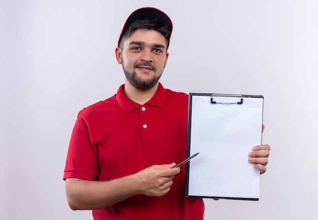 Young delivery man in red uniform and cap holding clipboard with blank pages pointing with pen to itasking for signature