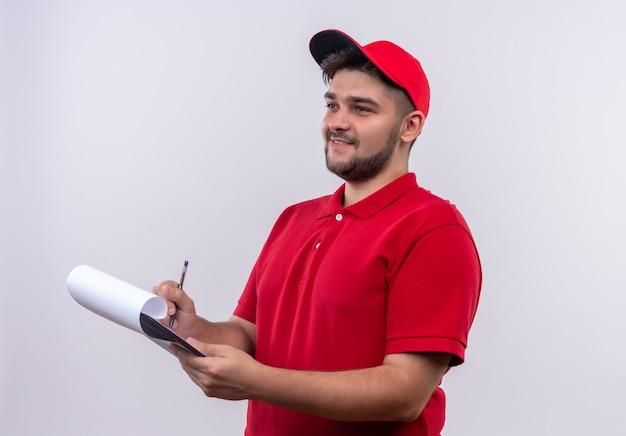 Giovane fattorino in uniforme rossa e cappuccio che tengono appunti con pagine bianche che scrivono sorridendo fiducioso