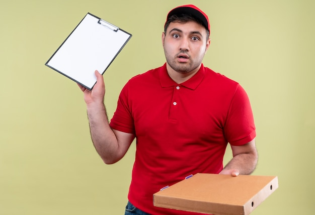 Young delivery man in red uniform and cap holding izza box and clipboard looking confused and uncertain standing over green wall