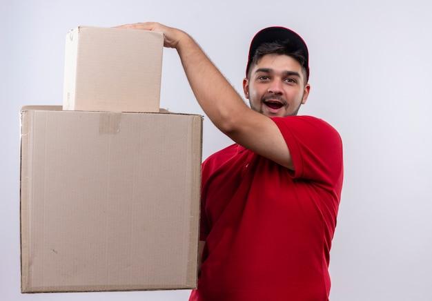 Giovane fattorino in uniforme rossa e berretto che tiene grandi scatole di cartone che sembrano sorpresi e stupiti