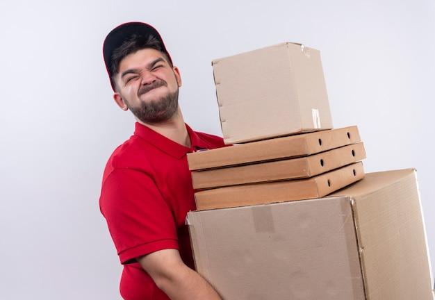 Giovane fattorino in uniforme rossa e cappuccio che tiene grandi scatole di cartone che soffrono di peso elevato