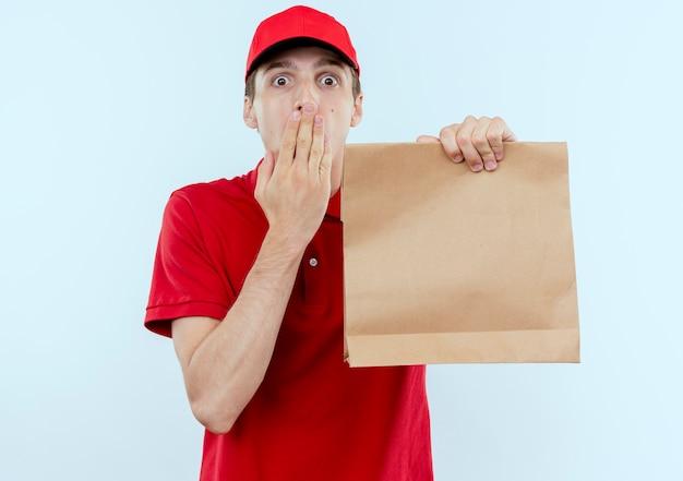 Giovane fattorino in uniforme rossa e cappuccio che tiene il pacchetto di carta guardando in avanti sorpreso che copre la bocca con la mano in piedi sul muro bianco