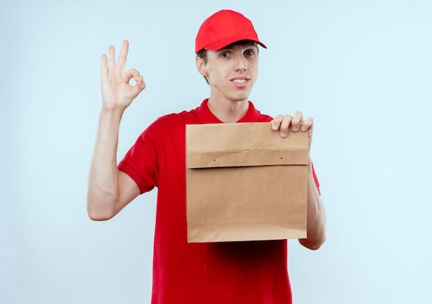 Giovane fattorino in uniforme rossa e cappuccio che tiene il pacchetto di carta guardando in avanti con un'espressione sicura che mostra il segno giusto che sta sopra il muro bianco