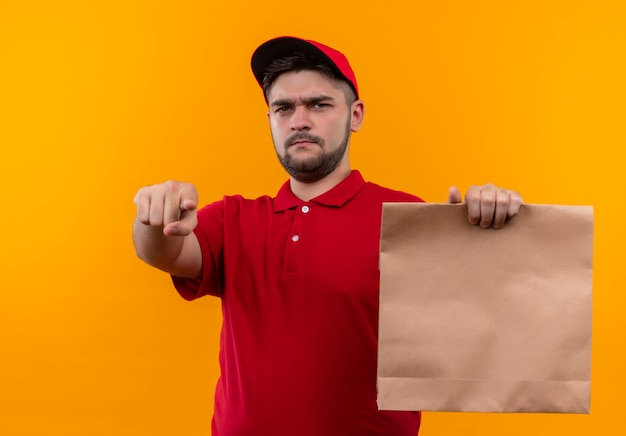 Young delivery man in red uniform and cap holding paper package pointing with finger to camera with angry face