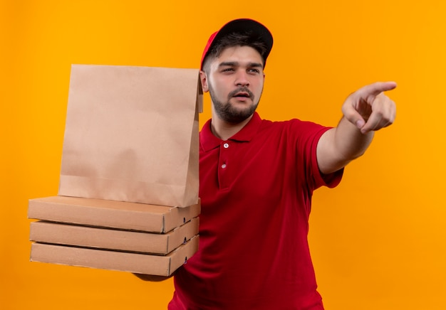 Young delivery man in red uniform and cap holding paper package and stack of pizza boxes pointing to something with skeptic expression