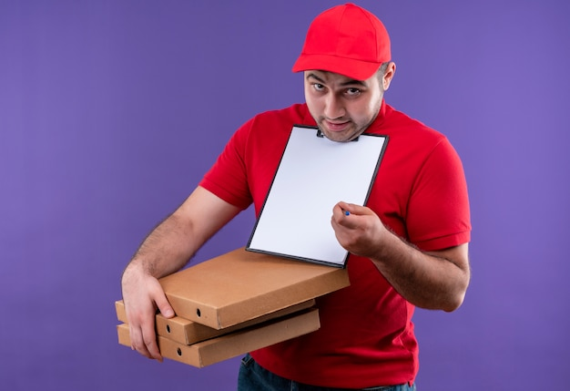 Young delivery man in red uniform and cap holding pizza boxes and clipboard with blank pages smiling confused asking for signature standing over purple wall