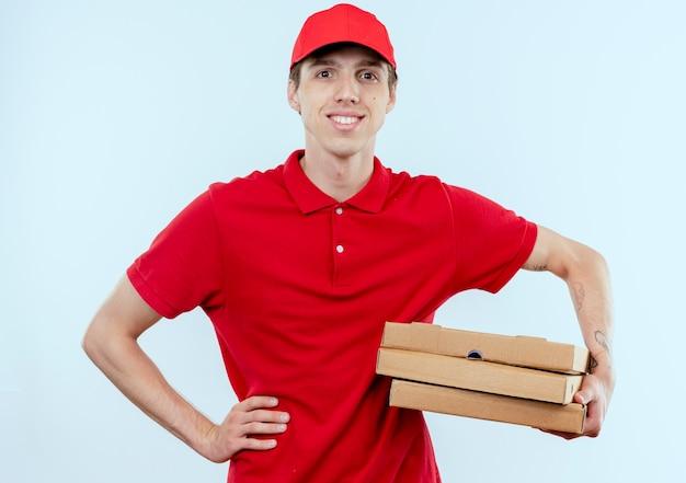 Giovane fattorino in uniforme rossa e cappuccio che tiene scatole per pizza guardando in avanti con espressione sicura in piedi sopra il muro bianco