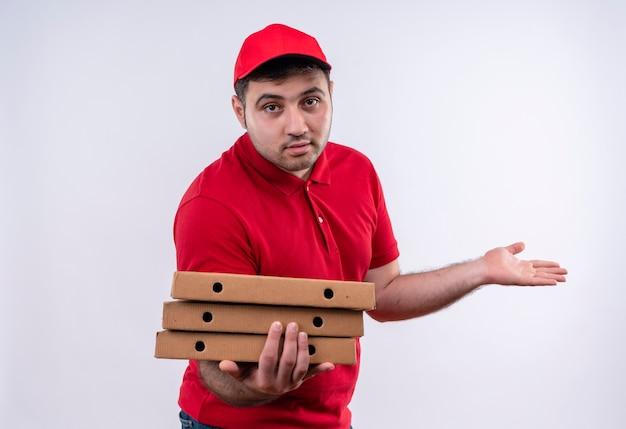 Giovane fattorino in uniforme rossa e cappuccio che tiene le scatole per pizza che presentano con il braccio della sua mano in piedi sul muro bianco
