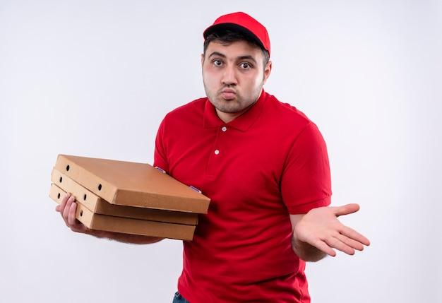 Giovane fattorino in uniforme rossa e cappuccio che tiene le scatole per pizza che si diffondono con il braccio di lato che sembra confuso in piedi sopra il muro bianco