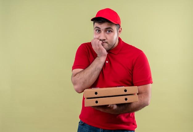 Il giovane fattorino in uniforme rossa e cappuccio che tiene le scatole della pizza ha stressato e nervoso chiodi mordaci in piedi sopra la parete verde