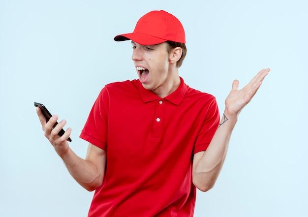 Giovane fattorino in uniforme rossa e cappuccio che tiene smartphone guardando sorpreso e confuso con il braccio alzato in piedi sopra il muro bianco