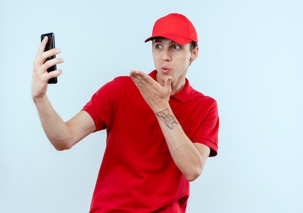 Giovane fattorino in uniforme rossa e cappuccio che tiene smartphone prendendo selfie sorridente che soffia un bacio in piedi sopra il muro bianco