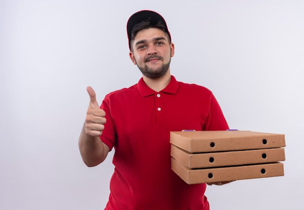 Young delivery man in red uniform and cap holding stack of pizza boxes looking confident smiling showing thumbs up