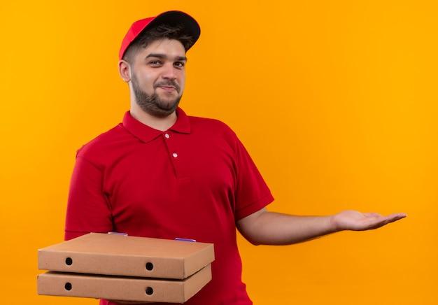 Giovane fattorino in uniforme rossa e cappuccio che tiene pila di scatole per pizza che presentano con il braccio oh il suo spazio della copia della mano