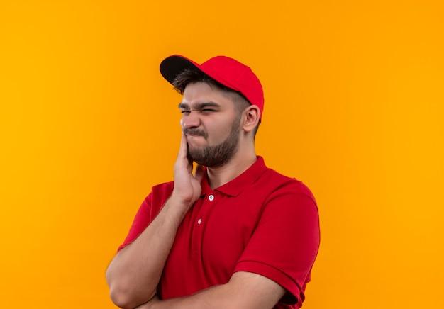 Giovane fattorino in uniforme rossa e berretto che osserva da parte confuso e molto ansioso