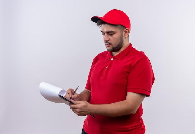 Giovane fattorino in uniforme rossa e cappuccio guardando appunti con pagine di plancia che scrivono con faccia seria