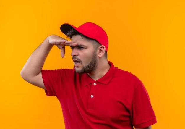 Giovane fattorino in uniforme rossa e berretto che guarda lontano con la mano sopra la testa per guardare qualcosa