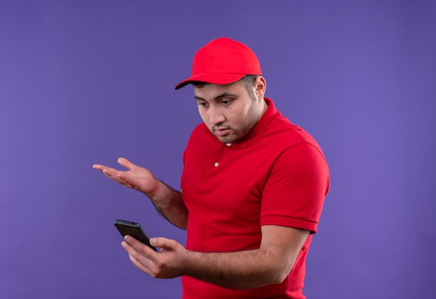 Young delivery man in red uniform and cap looking at screen of his smartphone confused and disappointed standing over purple