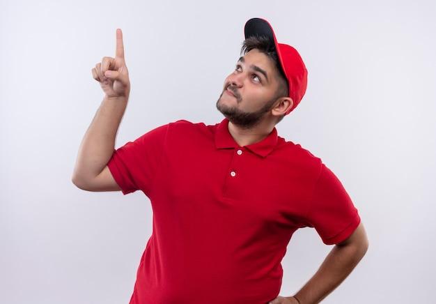 Giovane fattorino in uniforme rossa e cappuccio che osserva in su incuriosito e sorridente rivolto verso l'alto con il dito indice