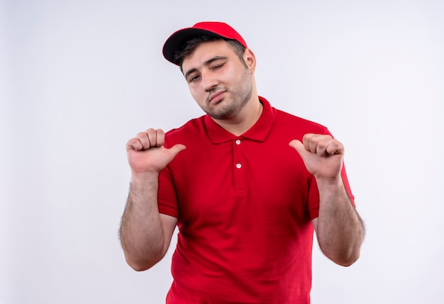 Young delivery man in red uniform and cap pointing with thumbs to himself, self-satisfied and proud standing over white wall
