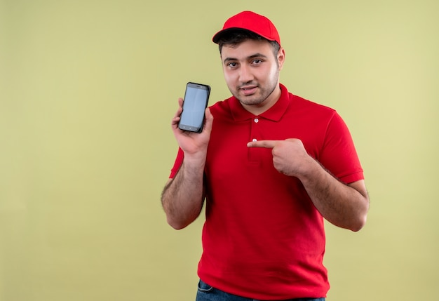 Young delivery man in red uniform and cap showing smartphone pointing with finger to it looking confident standing over green wall