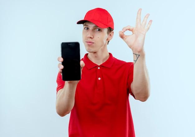 Giovane fattorino in uniforme rossa e cappuccio che mostra smartphone che mostra segno giusto in piedi sopra il muro bianco