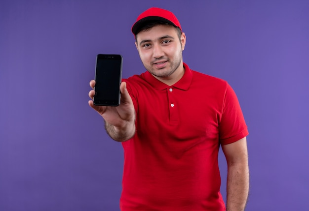 Young delivery man in red uniform and cap showing smartphone smiling confident standing over purple wall