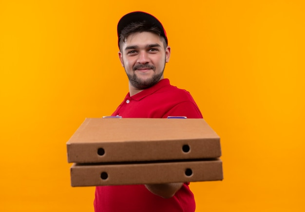 Young delivery man in red uniform and cap showing stack of pizza boxes smiling confident
