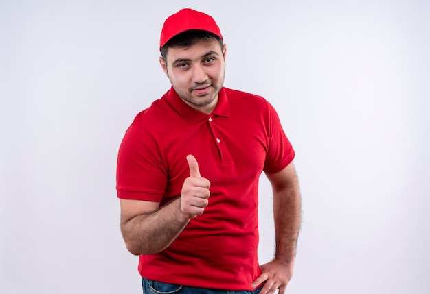 Young delivery man in red uniform and cap smiling cheerfully showing thumbs up standing over white wall