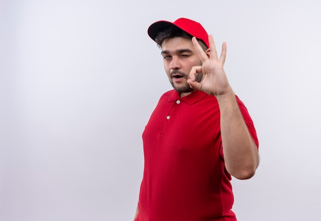 Young delivery man in red uniform and cap smiling confident winking showing ok sign