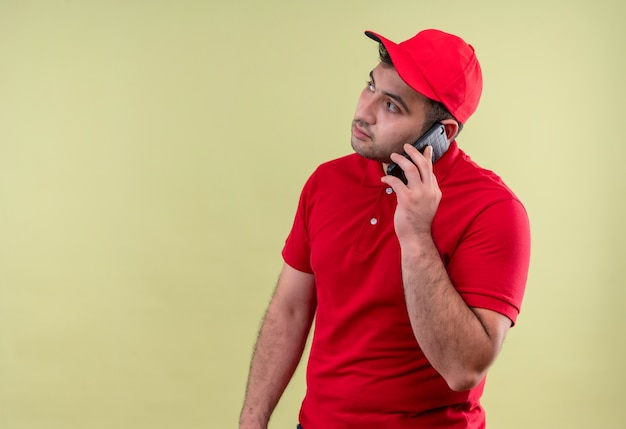 Young delivery man in red uniform and cap talking on mobile phone looking aside with serious face standing over green wall