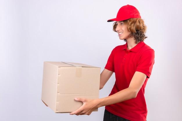 Giovane uomo di consegna in uniforme rossa che dà la scatola di cartone a un cliente sorridente amichevole sopra fondo bianco isolato