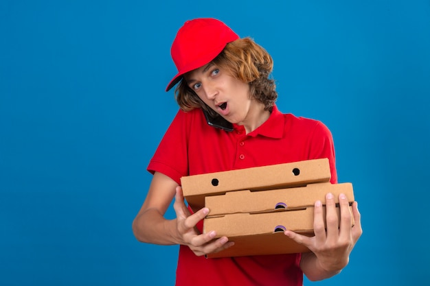 Giovane uomo di consegna in uniforme rossa che tiene scatole per pizza mentre parla al telefono cellulare guardando sorpreso su sfondo blu isolato