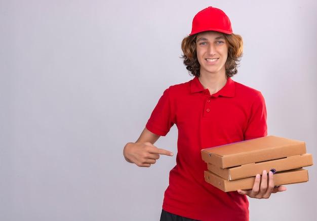 Giovane uomo di consegna in uniforme rossa che punta a scatole per pizza in mano guardando la telecamera sorridendo allegramente su sfondo bianco isolato