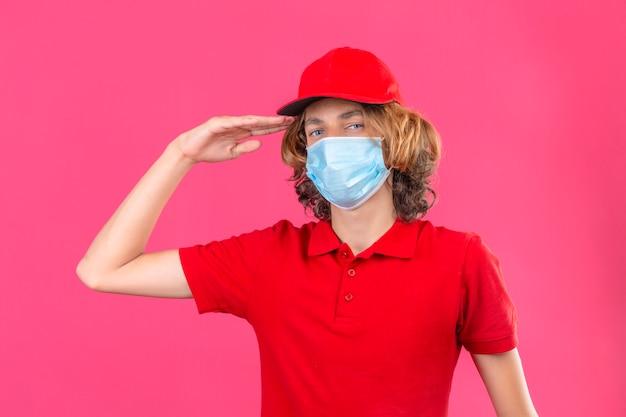 Giovane uomo di consegna in uniforme rossa che indossa la mascherina medica salutando guardando fiducioso in piedi su sfondo rosa isolato