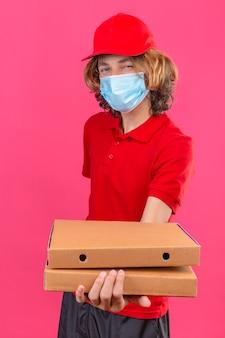 Giovane uomo di consegna in uniforme rossa che indossa la mascherina medica che allunga le scatole per pizza sorridente amichevole che sta sopra fondo rosa isolato
