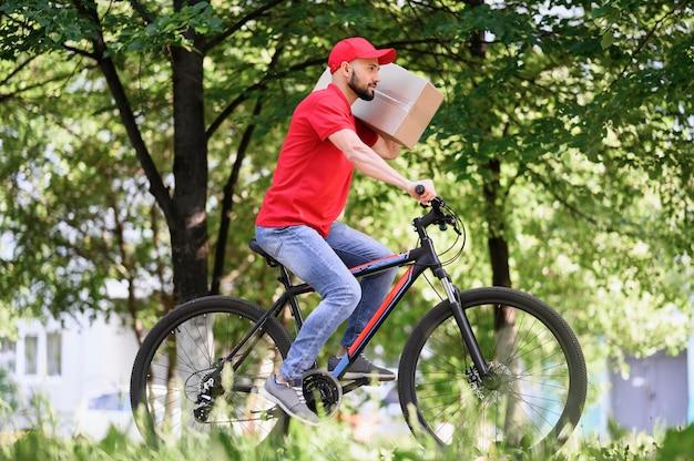 Giovane uomo di consegna in sella a bicicletta con pacco
