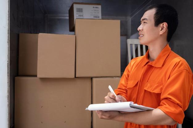 配達のために小包をスケジュールする若い配達人
