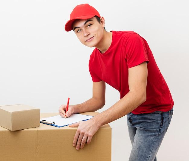 Молодой доставщик подписывает документы