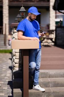 Молодой доставщик ждет клиента на открытом воздухе