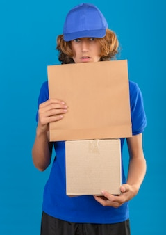 Молодой курьер в синей рубашке поло и кепке держит картонную коробку и бумажный пакет с удивленным видом, стоя на изолированном синем фоне