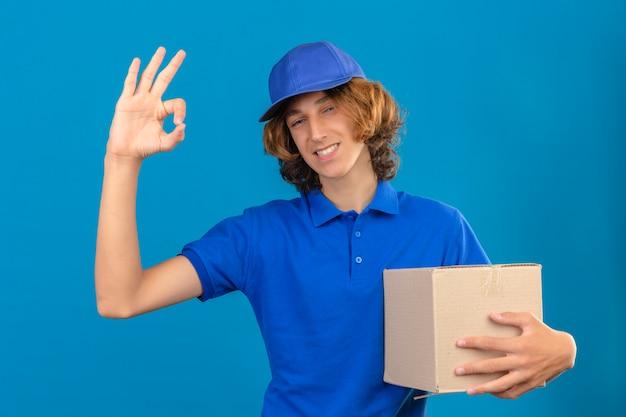 青いポロシャツと段ボール箱を持って若い配達人身に着けている段ボール箱okの標識をやっている分離の青い背景にフレンドリーな笑顔
